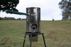 This image is a Tlud Biochar Cooking Stove with Biochar Industries forest in the back ground